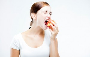 Woman holding and biting red apple, Healthy teeth