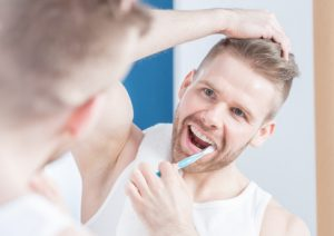 Handsome guy brushing his teeth